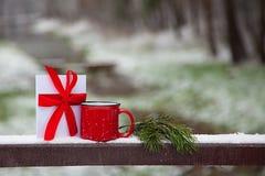 红色杯子和一张卡片在雪桥梁在一个冬天停放 库存照片