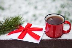 红色杯子和信件在雪桥梁在一个冬天停放 库存图片