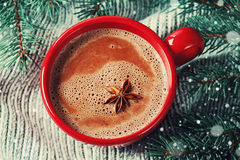 红色杯子热的可可粉或热巧克力在被编织的背景与杉树,传统饮料冬时的 库存照片