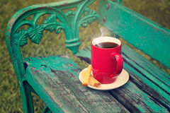 红色杯子用在老绿色长木凳的饼干在庭院背景中 图库摄影