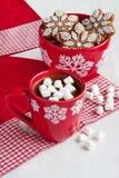 红色杯子用热巧克力和蛋白软糖和姜饼曲奇饼 免版税库存照片