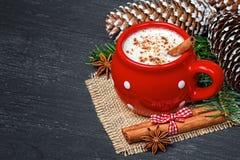 红色杯子用热的白色巧克力和桂香 免版税图库摄影