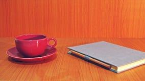 红色杯子&笔记本在木背景 免版税库存照片