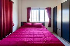 红色枕头和红色毯子有红色帷幕的在卧室与 免版税库存照片