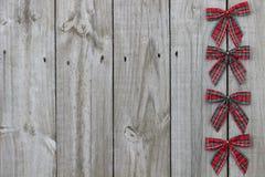 红色格子花呢披肩鞠躬在木标志的边界 图库摄影