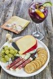 红色桑格里酒大酒杯与一个乳酪盘子的用开胃菜 免版税库存照片