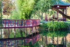红色桥梁和眺望台由池塘 图库摄影