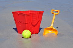 红色桶锹和球在海滩 免版税库存照片
