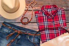 红色检查衬衣、牛仔裤、皮革帽子、袋子和传送带 图库摄影