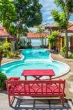 红色椅子和桌在游泳池边缘  免版税库存图片