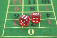 红色模子的卷在一个比赛表上的在赌博娱乐场 图库摄影