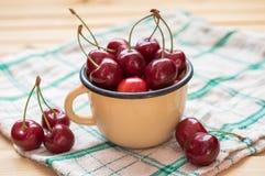 红色樱桃在黄色杯子和在与桌布的木桌上 库存照片