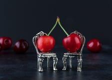 红色樱桃夫妇在两把银色椅子的与被弄脏的cherrie 免版税库存照片