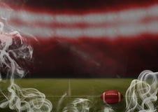 红色橄榄球球在体育场内 库存照片