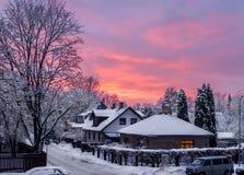 红色橙色冬天天空-日落在小多雪的镇 库存照片