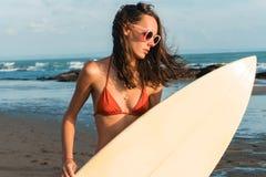 红色比基尼泳装和太阳镜的年轻美丽的妇女在手上拿着在海洋海滩的一朵海浪在日落 库存照片