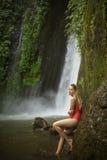 红色比基尼泳装和瀑布的妇女 免版税库存照片