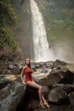 红色比基尼泳装和瀑布的美丽的妇女 免版税图库摄影