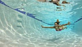 红色比基尼泳装的游泳的妇女在水面下 免版税库存照片