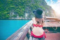 红色比基尼泳装的美丽的女孩在小船 免版税库存照片