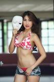 红色比基尼泳装的年轻美丽的亚裔妇女有短裤的 免版税图库摄影