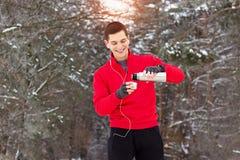 红色毛线衣倾吐的茶的英俊的微笑的运动员从热水瓶和听的音乐 室外的活动 免版税库存照片