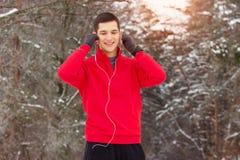 红色毛线衣听的音乐和身分的英俊的微笑的运动员在森林 室外的活动 免版税库存图片