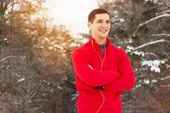 红色毛线衣听的音乐和身分的英俊的微笑的运动员在森林 室外的活动 免版税图库摄影