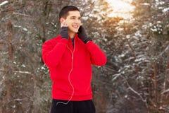 红色毛线衣听的音乐和身分的英俊的微笑的运动员在森林 室外的活动 免版税库存照片