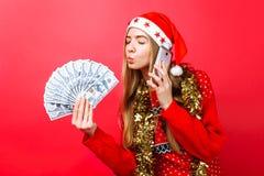 红色毛线衣和圣诞老人帽子的愉快的女孩谈话在电话和举行金钱手中设法的亲吻他们,在红色背景 免版税图库摄影