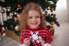 红色毛线衣的愉快的小女孩坐在圣诞树下并且拿着雪花 免版税库存照片
