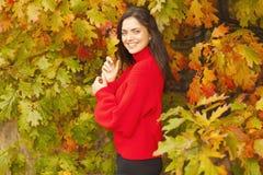红色毛线衣的美丽的妇女在公园 免版税库存照片