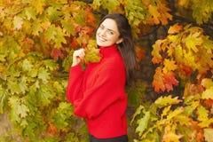 红色毛线衣的美丽的妇女在公园 库存照片