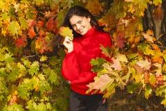 红色毛线衣的美丽的妇女在公园 免版税图库摄影