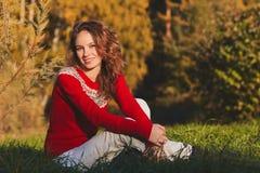 红色毛线衣的美丽的少妇在秋天公园 免版税库存照片