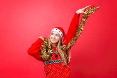 红色毛线衣的舞女和圣诞老人帽子,获得与闪亮金属片的乐趣在脖子,庆祝在红色背景的新年 库存图片