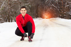 红色毛线衣的英俊的微笑的运动员栓他的运动鞋鞋带  室外的活动 免版税库存图片