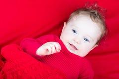 红色毛线衣的逗人喜爱的婴孩在红色毯子下 图库摄影