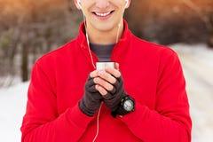 红色毛线衣饮用的茶的英俊的微笑的运动员和听的音乐在公园 室外的活动 免版税库存照片