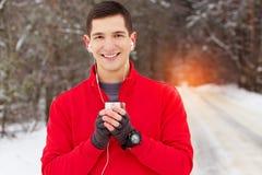 红色毛线衣饮用的茶的英俊的微笑的运动员和听的音乐在公园 室外的活动 库存照片