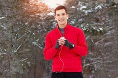 红色毛线衣饮用的茶的英俊的微笑的运动员和听的音乐在公园 室外的活动 图库摄影