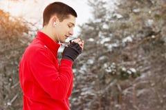 红色毛线衣饮用的茶的年轻和英俊的运动员和听的音乐在公园 室外的活动 图库摄影