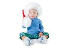 红色毛茸的圣诞老人帽子的逗人喜爱的小男孩在白色背景 免版税图库摄影