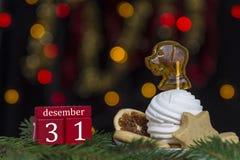 红色求甜点历日12月31日,板材用蛋白软糖和焦糖的立方当黄色和红色bokeh光狗背景  免版税库存照片