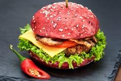 红色汉堡包用在石桌上的辣椒有黑背景 快餐膳食 可口汉堡包 美食的汉堡包 免版税库存图片