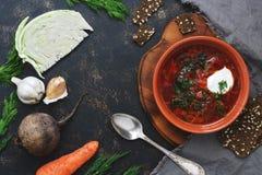 红色汤,圆白菜,甜菜,红萝卜,葱,大蒜,黑暗的表面上的黑麦薄脆饼干与文本的空间 顶视图 免版税库存图片