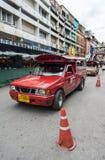 红色汽车出租汽车通过正在寻找顾客的街道运行 免版税库存照片