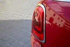 红色汽车后方车灯的片段在铺路石背景的  免版税图库摄影