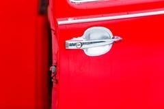 红色汽车把柄特写镜头 被打开的汽车门 库存照片