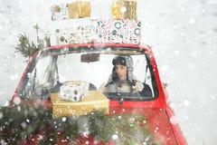 红色汽车的女孩有圣诞节礼物的 库存照片